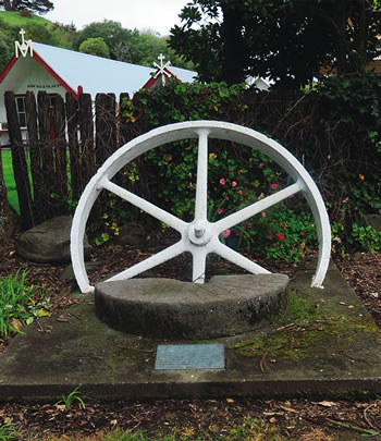 The plaque reads: This wheel and stone were once part of the Pukekaraka flour mill erected about 1854 under the direction of Father Comte s.m. The mill stood on the bank of the Waitohu River on property now owned by Mr Ray Taylor who donated these remains for erection on the site of the Pukekaraka Mission. Otaki Historical Society Inc. 1985